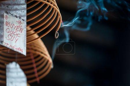 Photo pour Vue rapprochée du bâton d'encens en spirale brûlant avec de la fumée bleue descendant sur fond sombre. rituels religieux traditionnels dans le temple. Religion et traditions de l'Orient. Arôme et parfum . - image libre de droit
