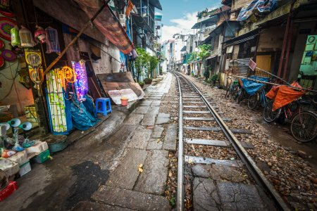 Photo for Perspective view of railway running along narrow street with houses in Hanoi, Vietnam. Unusual solution of transport problem. Dangerous neighborhood for people. Travelling and tourism. - Royalty Free Image