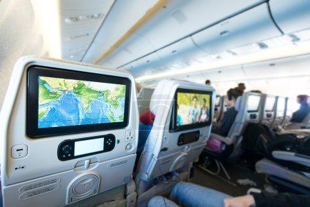 Photo pour Cabine avec des personnes à bord regardant des écrans LCD. Carte de vol colorée et film sur écran. Intérieur de l'avion de passagers. Voyage rapide et confortable. Surveiller comme moyen d'obtenir du plaisir et de l'information . - image libre de droit