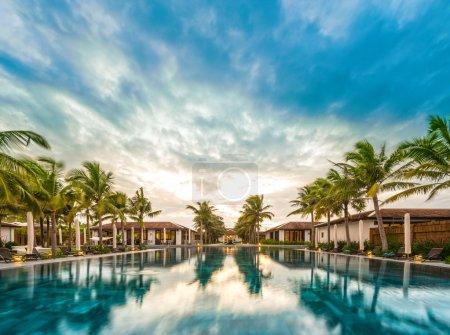 Photo pour Maisons et piscine au milieu de la station balnéaire au Vietnam, Asie. Reflet des palmiers verts et du ciel bleu avec des nuages dans l'eau. Belle station touristique. Architecture moderne, extérieur de luxe. Lumineux jour d'été . - image libre de droit