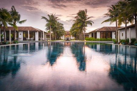 Foto de Casas y piscina en medio del complejo en Vietnam, Asia. Reflejo del cielo púrpura con nubes en el agua. Hermoso complejo turístico. Arquitectura moderna, exterior de lujo. Día de verano brillante . - Imagen libre de derechos
