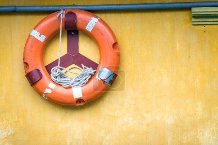 orangefarbener alter Rettungsring mit Seil