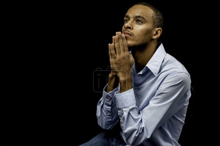 Photo for Nice isolation of a young african american black male praying with plenty of space for custom text - Royalty Free Image