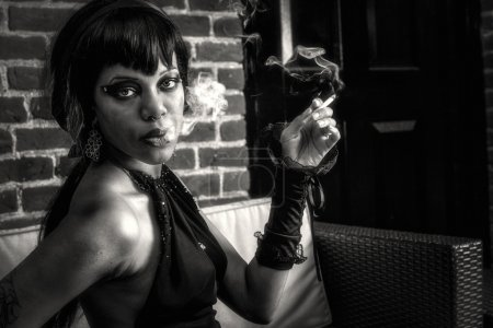 Photo pour Sexy femme gothique afro-américaine fumant. Éclairage créatif et dramatique avec fumée, yeux sexy, look séduisant, photo noir et blanc - image libre de droit