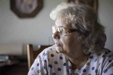 Photo pour Femme âgée dans un cadre naturel à la maison. Faible profondeur de champ brouillant le fond. Regard de pensée ou sentiment de solitude . - image libre de droit