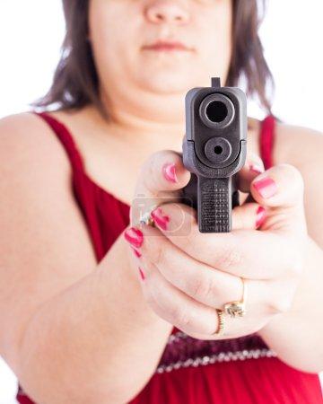 Photo pour Femme hispanique blanche tenant une arme pointée vers l'écran. Profondeur de champ faible en mettant l'accent sur le canon. Robe rouge avec une femme moyenne se protégeant avec une arme . - image libre de droit