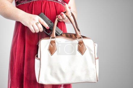 Photo pour Femme blanche dans une robe rouge, enlever une petite arme de poing de son sac à main. dissimuler l'arme carry pour prootection. mise au point des genoux au cou, il pourrait être utilisé pour plusieurs siècles. - image libre de droit