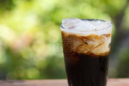 Photo for Iced coffee with milk on a wooden table. - Royalty Free Image