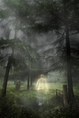 Photo pour Figure fantomatique d'un vieux gentleman marchant dans un cimetière boisé - image libre de droit
