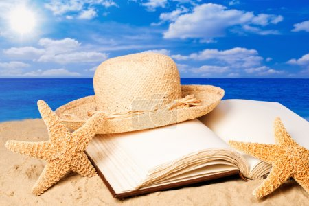 Photo for Straw sunhat lying on an open book on sandy beach in summe - Royalty Free Image