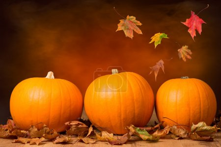 Photo for Three pumpkins with fall leaves with seasonal background - Royalty Free Image