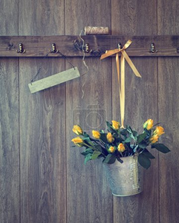 Photo for Bucket filled with yellow roses hanging on wall with blank sign for your text - Royalty Free Image