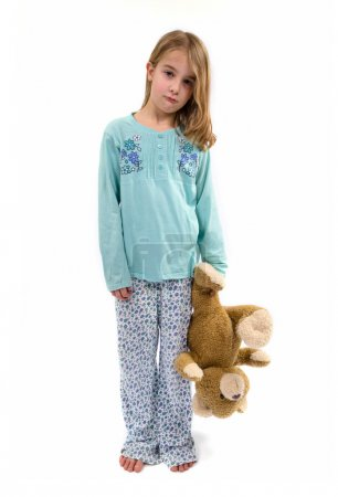 Sad girl in pajamas holding teddy