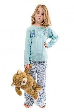 Girl in pajamas with teddy bear
