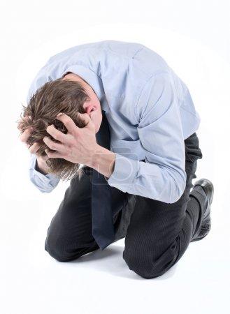 Photo pour Stressé ou homme d'affaires désespérée sur ses genoux avec les mains dans ses cheveux - image libre de droit