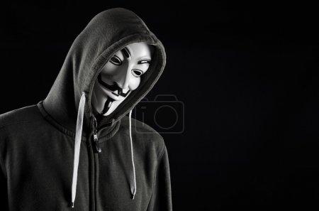 Hooded man wearing V for Vendetta mask...