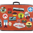Old worn suitcase with travel stickers from around...