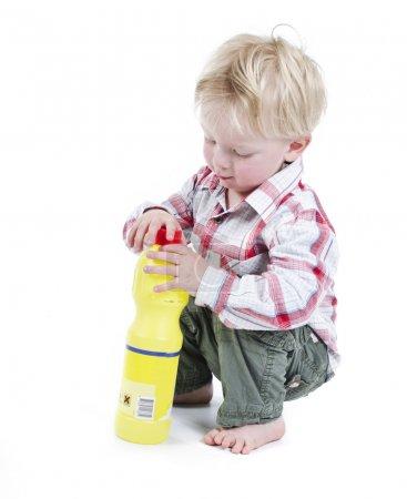 Photo pour Jeu d'enfants avec des matériaux de nettoyage toxiques concept de danger ou négligence parentale mauvaise - image libre de droit