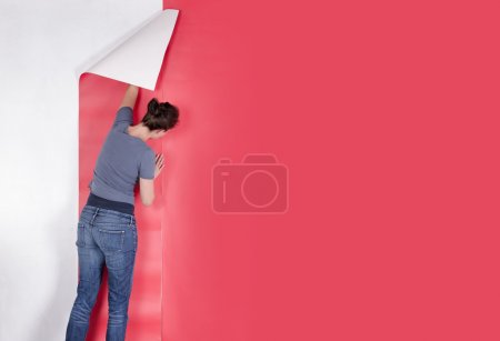 Woman hanging red wallpaper on white wall. Decorat...