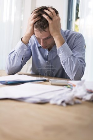 Photo for Worried man doing finances. Stressed because he can't pay the bills - Royalty Free Image
