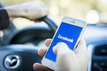Photo for Man using facebook outdoors. Social media while driving risking ticket. - Royalty Free Image
