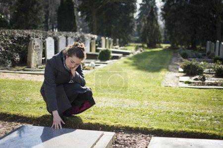 Photo pour Femme au cimetière devant la tombe du parent décédé. triste, deuil. - image libre de droit