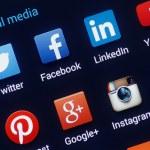 Social media icons on smartphone screen. Closeup o...