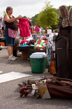 Female Vendor Gets Merchandise Ready At Garage Sale