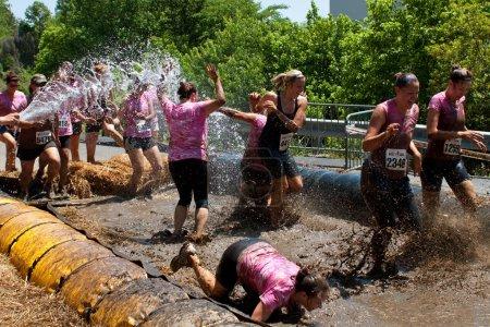 Photo pour Atlanta, ga, é.-u. - 28 avril : un groupe de femmes non identifiées en compétition dans la boue sale fille course, éclabousser dans le bourbier et obtenir trempé avec un tuyau d'incendie qu'ils près de la ligne d'arrivée de la femme uniquement de course - image libre de droit