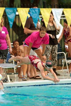 Photo pour Lawrenceville, ga, é.-u. - 14 juin : un nageur plongées dans la piscine pour nager sa jambe d'une course de relais pendant une baignade de quartier se réunir entre trois équipes de natation les jeunes femelles. - image libre de droit