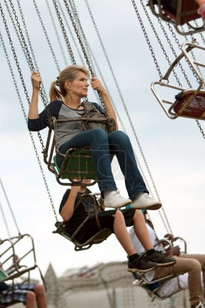 Adult Woman Rides Swings At County Fair