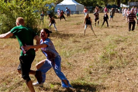 Female Zombie Nurse Chases Runner in Scary 5K Obstacle Race