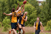 Players Jump To Catch Ball In Australian Rules Football Game