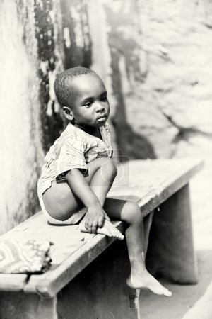 Young boy from Togo sits on a bench