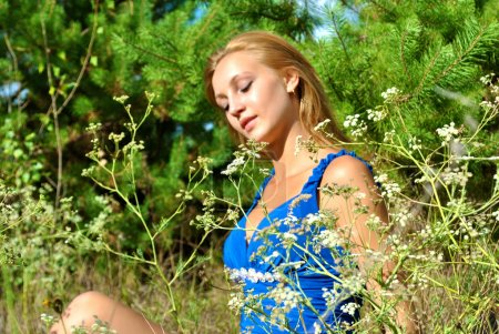 Amazing blonde sexual female model in a blue dress sits among the grass