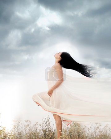 Portrait of beautiful young woman standing in a field with wind blowing her long hair