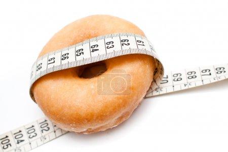 Photo for Donuts en fondo blanco con una cinta metrica, contrario a la dieta y adelgazar - Royalty Free Image