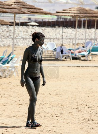 Young caucasian woman taking mud treatment outdoor