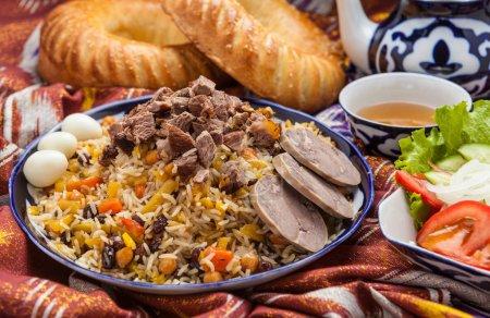 Uzbek national food in traditional fabric adras. �...