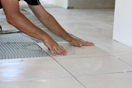 Photo for A male tiler laying light color floor tiles - Royalty Free Image