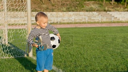 Little boy waiting to play soccer