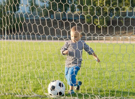 Little boy kicking a goal