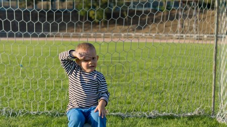 Little boy sitting in goalposts