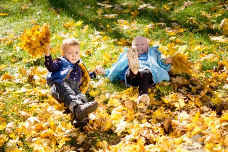 Kids frolicking in yellow autumn leaves