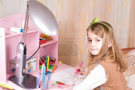 Cute little girl seated at her pink desk in her be...