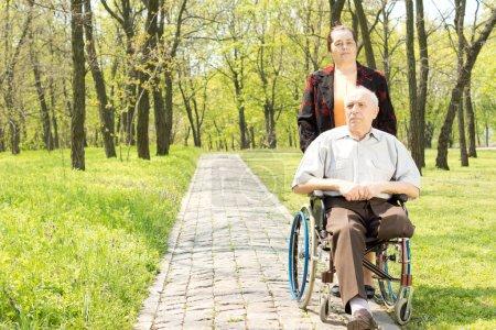 Photo pour Femme marchant d'un handicapé en fauteuil roulant qui a eu une jambe amputée par un paisible parc boisé rural - image libre de droit