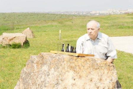 Photo pour Senior homme jouant aux échecs avec son échiquier en équilibre sur un rocher reste assis à l'extérieur dans la campagne, profiter du soleil - image libre de droit