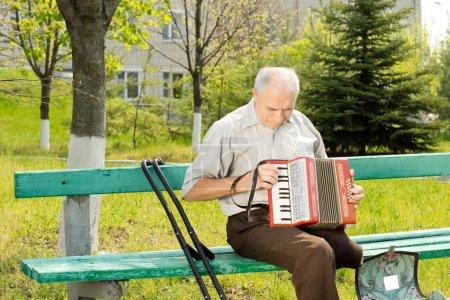 Photo pour Homme senior handicapé avec une jambe amputée au-dessus du genou, assis sur un banc de parc, jouer de l'accordéon - image libre de droit