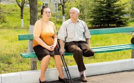 Photo pour Homme avec pied cassé, assis sur le banc de parc avec sa femme - image libre de droit