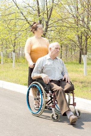 Photo pour Femme poussant senior homme en fauteuil roulant dans le parc - image libre de droit